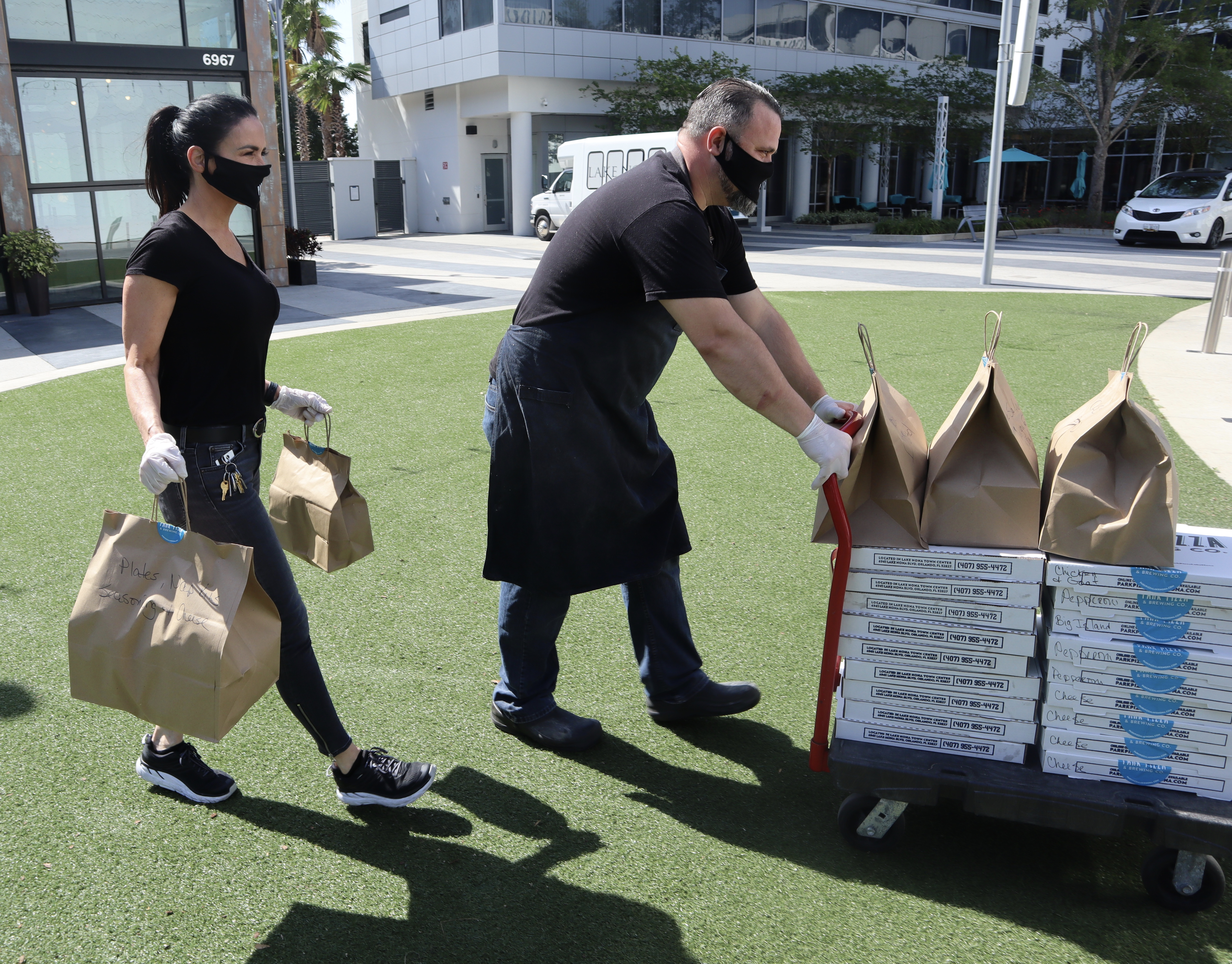 Park Pizza & Brewing Company employees roll out a cart full of pizzas to be delivered via self-driving shuttle tohealthcare workers in Orlando, Florida.